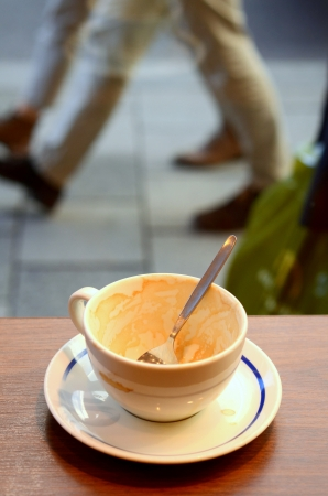 Urban Image Of An Empty Coffee Cup In A Cafe With People Rushing Passed photo