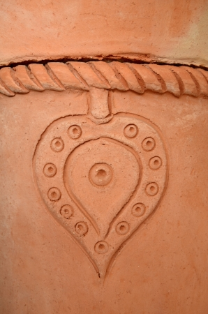 cultural artifacts: Heart Detail On A Rustic Terracotta Pot