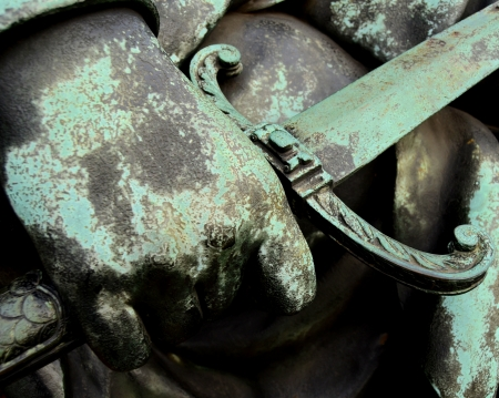 corroded: Details Of A Soldiers Hand Holding A Sword On A Bronze Statue