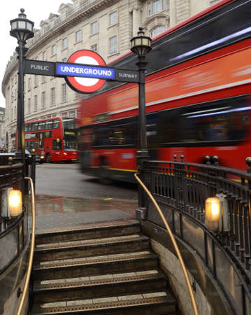Typical London Scene Of A Red Bus Speeding Past An Undergound Station