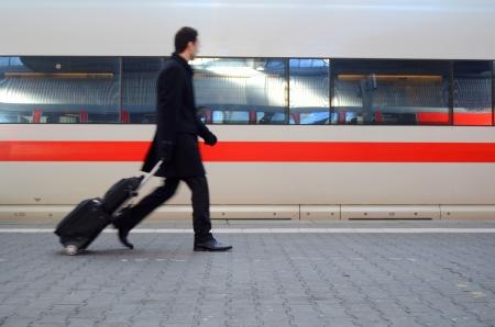 estacion de tren: Desenfoque de movimiento de un hombre corriendo a coger un tren en una estación