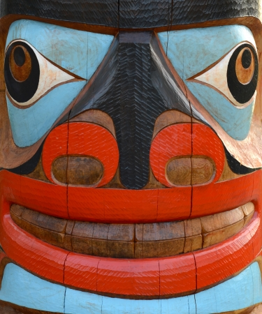 the totem pole: Detail Of A Brightly Painted Face On A Totem Pole Stock Photo