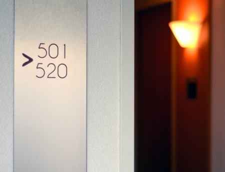 hotel door: Travel Image Of A Hotel Corridor With Light And Sign Stock Photo