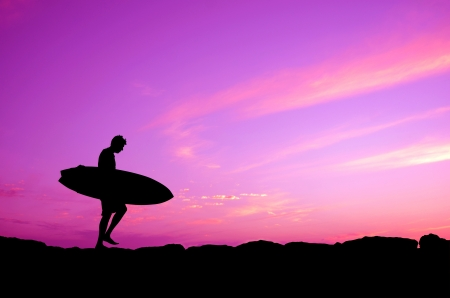 surfing beach: Vacation Silhouette Of A Surfer Carrying His Board Against A Purple Sunset