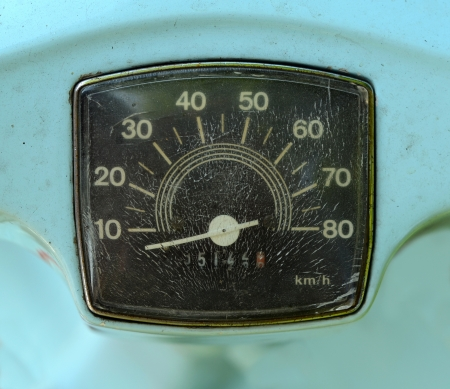 A Grungy Speedometer On A Sky Blue Scooter photo