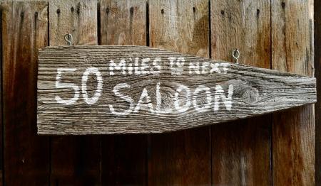 lejos: Wild West rústica de madera muestra que señala a continuación Saloon Foto de archivo