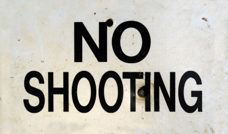 disobey: Grungy No Shooting Sign With Bullet Holes