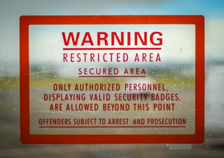 A Red Airport Security Restricted Area Warning Sign photo