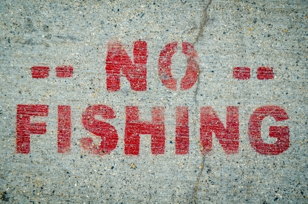 A No Fishing Sign Stamped Onto Cement By Ocean Or River photo