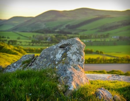 A Rolling Scottish Landscape At Sunset With Rock In Foreground photo