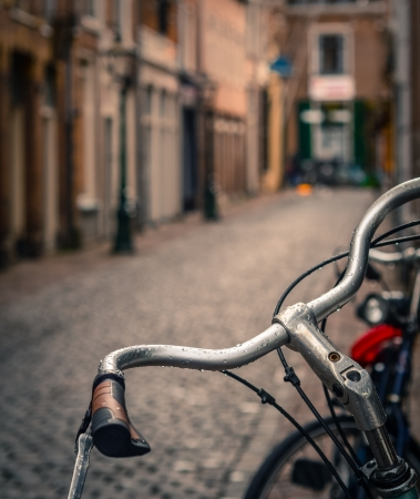 Scene Of A Bicycle In The Rain On A Cobbled European Backstreet Фото со стока