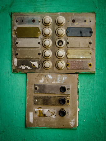 Rustic Old Apartment Intercom Buzzer Agaist Green Painted Wall photo