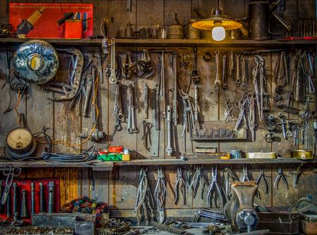 herramientas de carpinteria: Herramientas del vintage que cuelgan en una pared en un cobertizo para herramientas o taller