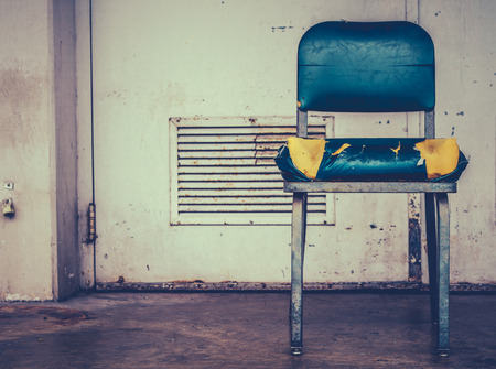 discarded metal: A Grungy Retro Damaged Chair Outside  A Workplace Stock Photo