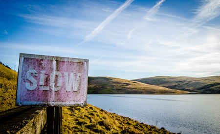 loosen up: Conceptual Image Of Rustic Slow Sign Beside Tranquil Scenic Lake