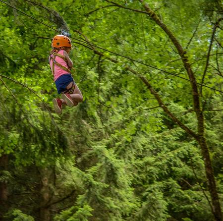 Chica joven en una tirolesa en un Parque de Aventura Forestal