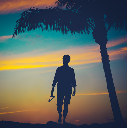 Retro Vintage Filtered Photo Of A Man Strolling On A Beach In Hawaii With Palm Tree At Sunset photo
