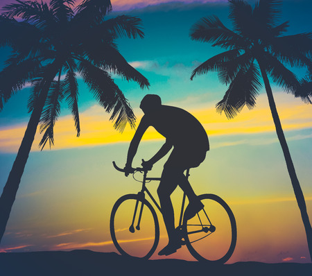 filtered: Retro Worn Style Photo Of A Man Cycling By Tropical Palm Trees Stock Photo