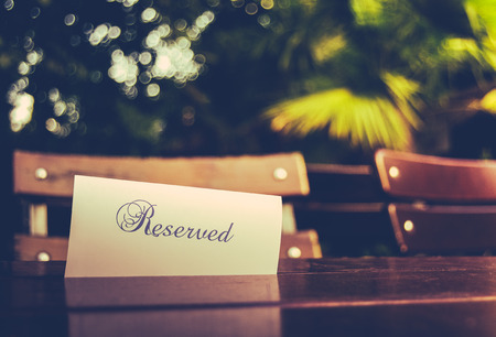 Vintage Styled Image Of A Reserved Sign On A Table At An Outdoor Restaurant photo