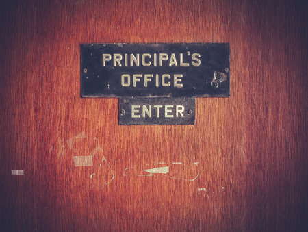 Retro Filtered Image Of A Grungy Principal's Office Door At A Public School In The USA Фото со стока