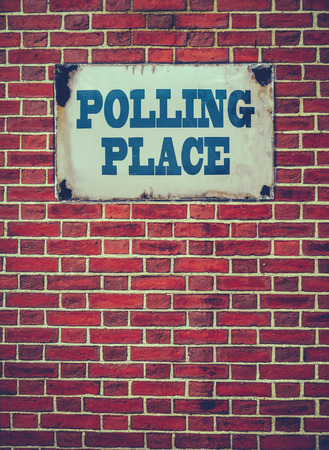 polling: Retro Filtered Sign For An Election Polling Place Or Station On A Red Brick Wall Stock Photo