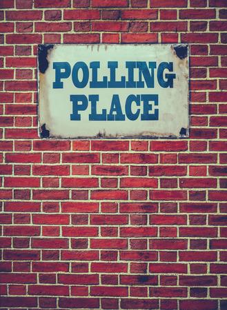 encuestando: Retro filtrada Sign For An Lugar de Votación Elección O estación en una pared de ladrillo rojo