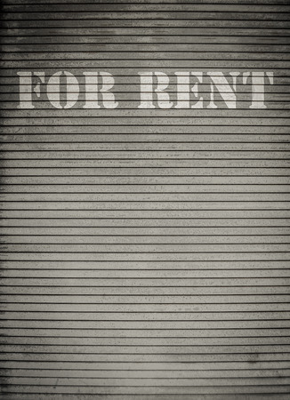 vacant: For Rent Sign On Dirty Scratched Store Roller Shutters