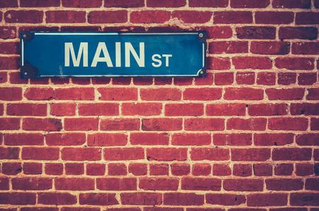 Retro Filtered fotografie Main Street podepsat na červené cihlové zdi Reklamní fotografie