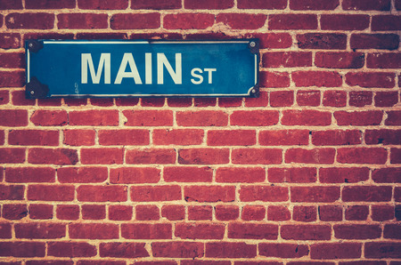 Retro Filtered Photo Of A Main Street Sign On A Red Brick Wall photo