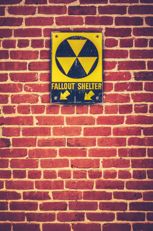 Retro Styled Nuclear Fallout Shelter Sign On A Red brick Wall photo