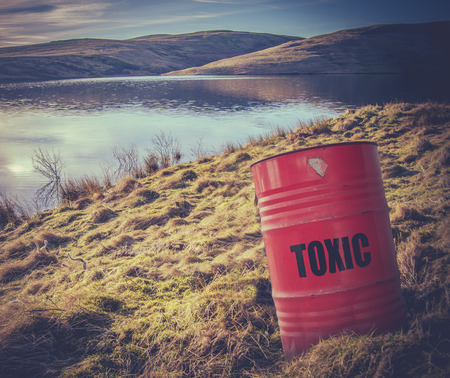 Conceptueel beeld van een Giftig Afval Barrel Of Drum Dichtbij Water In Het Platteland