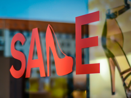A Sale Sign In A Shoe Store Window