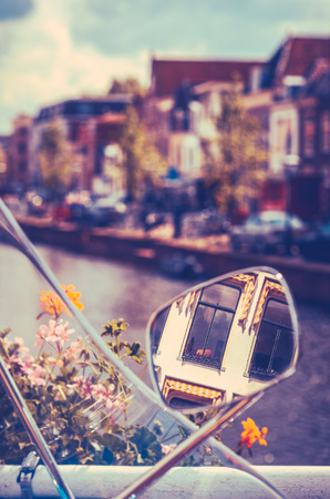 mirror on the water: Netherlands Apartment Reflected In Moped Mirror Near A Canal Stock Photo