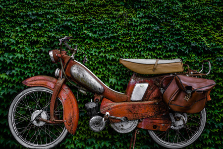60s: Vintage 60s French Moped Or Scooter With Pannier Bag And Flat Tyre Or Scooter Against An Ivy Background Stock Photo