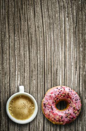 filiżanka kawy: Retro filtrowany Wizerunek różowy pączek i filiżanka kawy na wiejskim drewnianym stole z kopi?