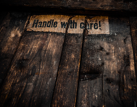 Grungy Filtered Handle WIth Care Sign On An Old Wooden Shipping Crate photo
