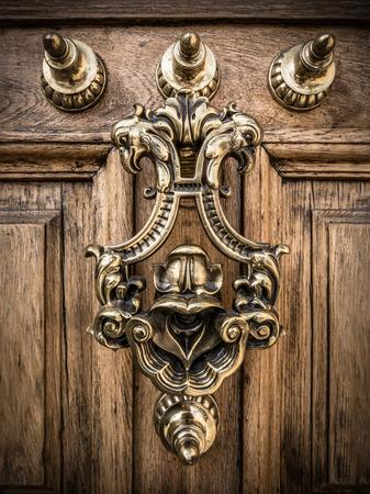 knocker: A Grand Ornate Brass Door Knocker On A Heavy Wooden Door In Spain