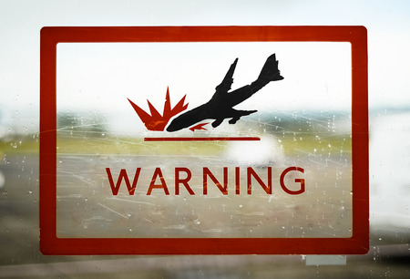 airport security: A Red Airport Security Warning Sign With Crashing Plane Stock Photo
