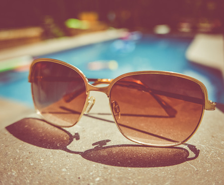Retro Style Image Of Sunglasses Beside A Swimming Pool