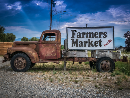 Sign For A Farmers Market On The Side Of A Vintage Rusty Truck Foto de archivo