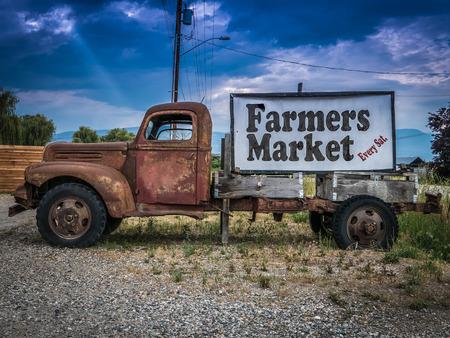 campesino: Regístrate para un mercado de agricultores en el costado de un camión oxidado de la vendimia Foto de archivo