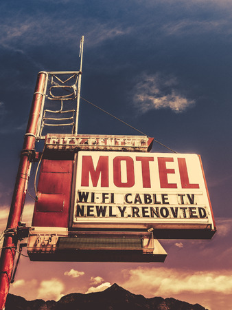 Retro Vintage Image Of Old Motel Sign In Small Town USA In The Mountains