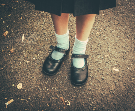 escuela primaria: Estilo retro de la imagen de los pies de la muchacha de la escuela en uniforme