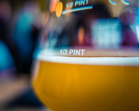 yellow to drink: Detail Of A Third Glass Pint Of Beer Or Ale In A Trendy Microbrewery Or Gastropub