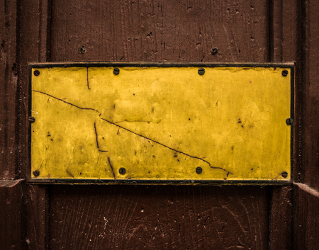 A Grungy Yellow Sign On A Wooden Door For Your Text Stock Photo
