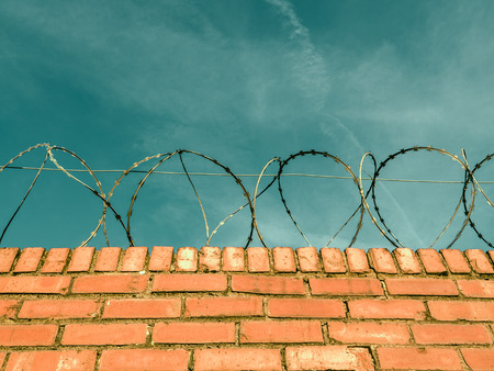 razor wire: Barbed Or Razor Wire On Top Of A Red Brick Wall Around Private Property
