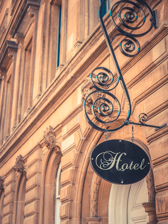 boutique hotel: Ornate Sign For Luxury Hotel Outside Beautiful Sandstone Building