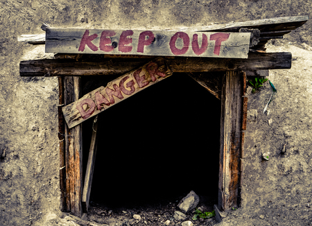 dangerous: Conceptual Image Of A An Entrance To An Old Mine Tunnel With Keep Out And Danger Signs