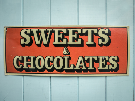 shop sign: Vintage Sign For Sweets And Chocolates In The Great Britain