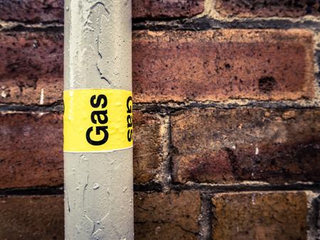 se�ales de seguridad: Detalle de una tuber�a de gas residenciales contra una pared de ladrillo rojo